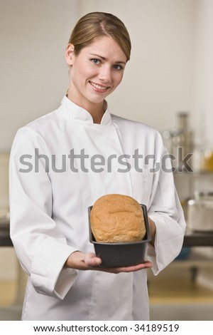A young woman is standing in a kitchen and holding out a loaf of bread.  She is smiling at the camera.  Vertically framed shot. - stock photo