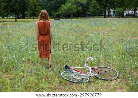 A young woman is standing in a meadow with a bicycle on the ground next to her - stock photo