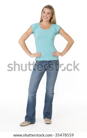 A young woman is standing in a room and smiling at the camera.  Vertically framed shot. - stock photo