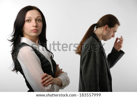 A young woman is standing in close pose and looking at the camera. In the background there is a disappointed man.  - stock photo