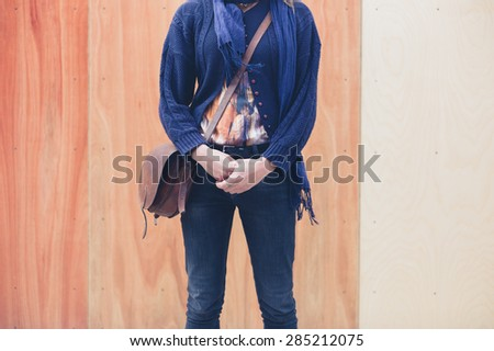 A young woman is standing in front of a wooden wall with two colors