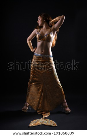 A young woman is standing in the stage costume of the mermaid. - stock photo