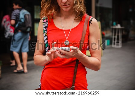 A young woman is standing in the street and is using her smart phone - stock photo