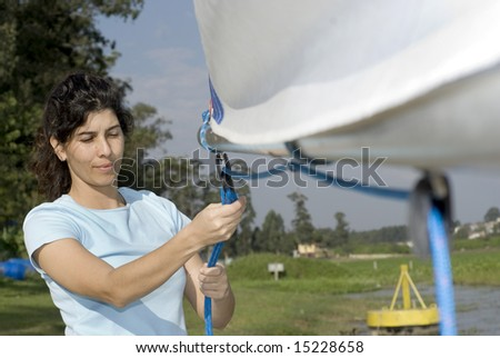 A young woman is standing next to her boat.  She is smiling and looking down at the rope she is pulling.  Horizontally framed shot. - stock photo