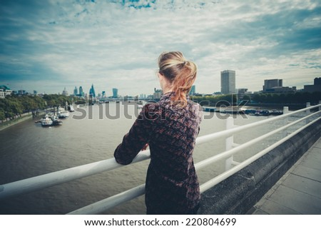A young woman is standing on a bridge in the city and is admiring the skyline