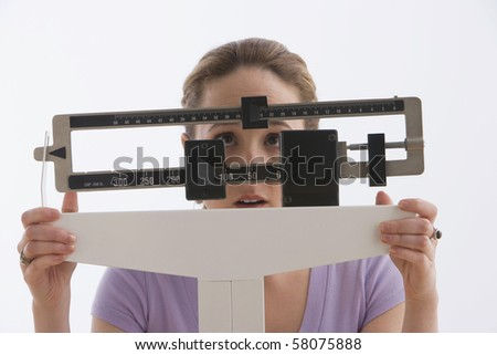 A young woman is standing on her scale and checking her weight. Horizontal shot. Isolated on white. - stock photo