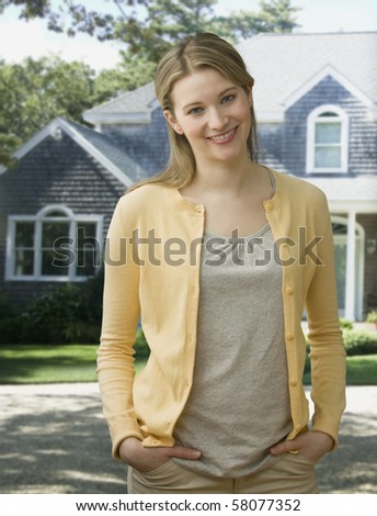 A young woman is standing outside in a residential neighborhood and smiling at the camera.  Vertical shot. - stock photo