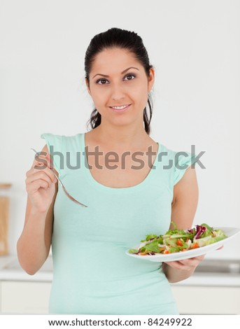 A young woman is standing with a salad in her kitchen