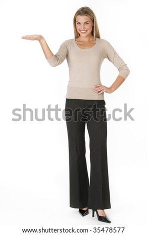 A young woman is standing with her arm outstretched and is smiling at the camera. Vertically framed shot. - stock photo