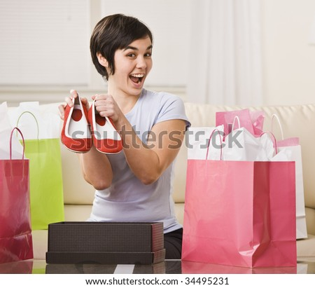 A young woman is surrounded by shopping bags and is holding out a pair of shoes.  She is smiling at the camera.  Square framed shot.