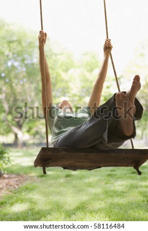 A young woman is swinging on a swing in a park setting.  Vertical shot. - stock photo