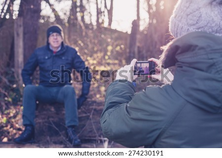 A young woman is taking a picture of a senior family member resting on a felled tree in a forest on a winter day - stock photo