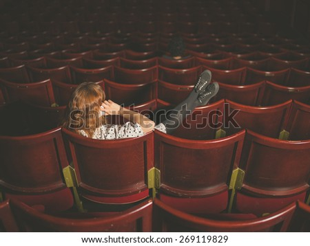 A young woman is talking on her phone in an auditorium - stock photo
