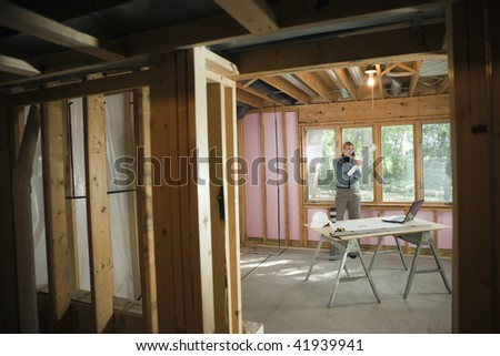 A young woman is talking on the phone at a construction site.  Horizontally framed shot. - stock photo