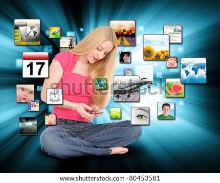 A young woman is texting on a phone with different photos coming out on a black, glowing background. - stock photo