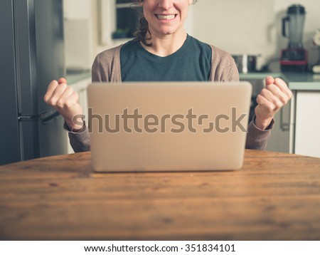 A young woman is using her laptop in a domestic kitchen and is doing a double  fist pump as she is getting excited