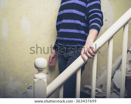 A young woman is walking down an old staircase in a house undergoing home improvements - stock photo