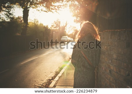 A young woman is walking into the sunset on an autumn day in the city - stock photo