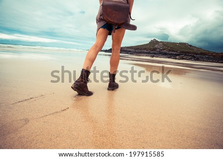 A young woman is walking on the beach and is leaving footprints - stock photo