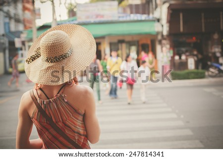 A young woman is walking on the street of an asian country on a sunny day - stock photo