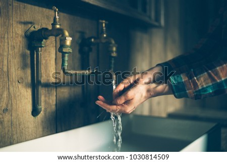 A young woman is washing her hands in a sink with brass faucets