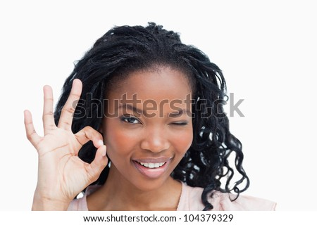 A young woman is winking and holding her hand in the okay sign against a white background - stock photo