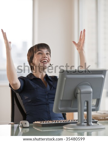 A young woman is working on a computer in an office.  She is smiling and looking up in the air.  Vertically framed shot. - stock photo