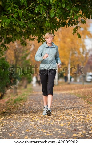 A young woman jogs along a path