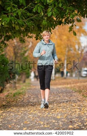 A young woman jogs along a path - stock photo