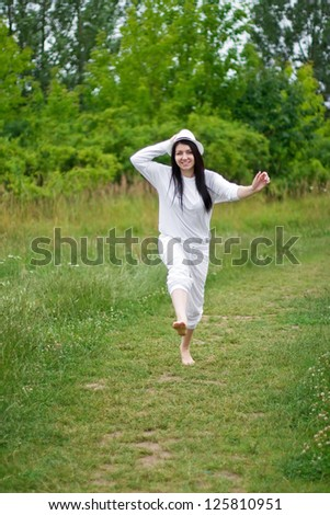A young woman joyously jumping and running in a summer setting
