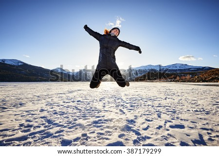a young woman jumping for joy on a frozen mountain lake - stock photo