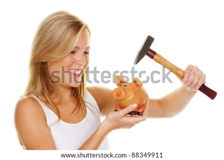 a young woman kills her piggybank with a hammer - stock photo