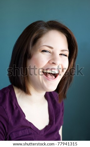 A young woman laughing hysterically. - stock photo