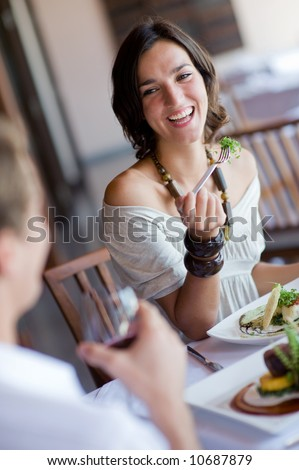 A young woman laughing whilst eating dinner at a restaurant - stock photo