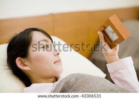 A young woman laying in bed and watching clock