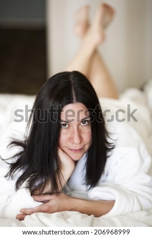 A young woman lays on a bed, relaxing in her plush bathrobe. - stock photo