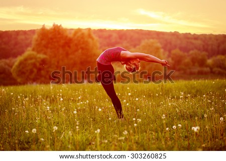 A young woman leans backward on evening meadow - stock photo