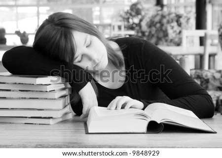 A young woman leans her head on a pile of books while studying. - stock photo