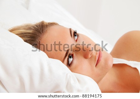 a young woman lies awake in bed. sleepless and thoughtful. - stock photo