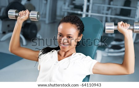 A young woman lifting free weights with a confident smile - stock photo
