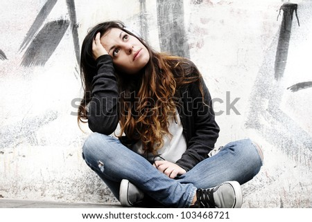 A young woman listening to melancholic Music and sitting on the pavement. - stock photo