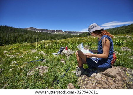 a young woman looking at a map in the mountains - stock photo