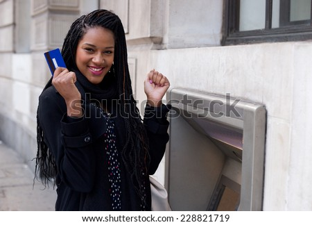 a young woman looking happy at the cash machine. - stock photo