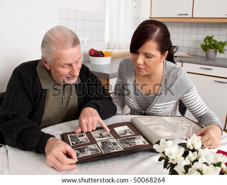 A young woman looks at a photo album with seniors - stock photo