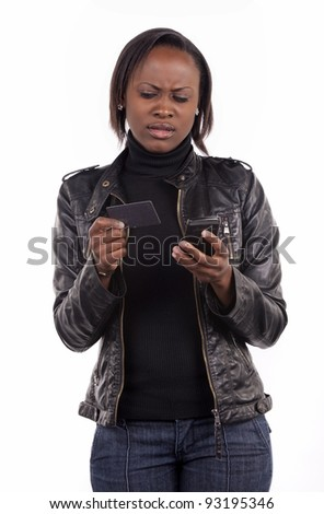 A young woman looks depressed after checking her bank balance on her mobile phone.