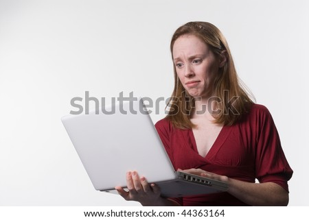 a young woman looks down at her laptop computer screen with a disconcerted look on her face