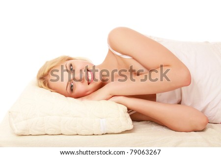 A young woman lying on a pillow, isolated on white
