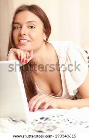 A young woman lying on the bed with laptop - stock photo