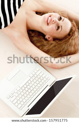 A young woman lying on the floor with a laptop - stock photo