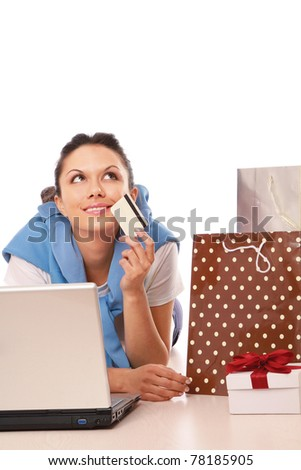 A young woman lying on the floor with a laptop, holding a credit card - stock photo